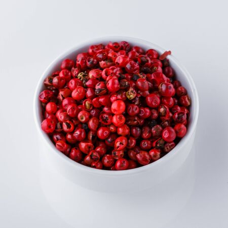 fragrant pink peppercorns on white acrylic background.