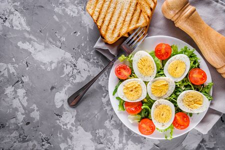 salad with boiled chicken eggs and cherry tomatoes on a stone background.