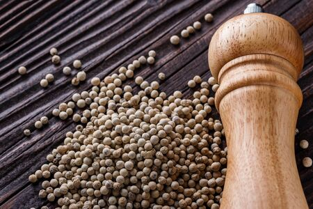 white peppercorns in wooden scoop on rustic background.