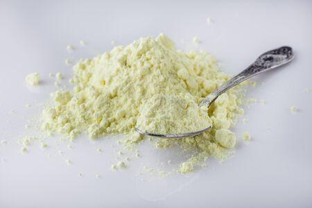purified sulfur powder on a white acrylic background.