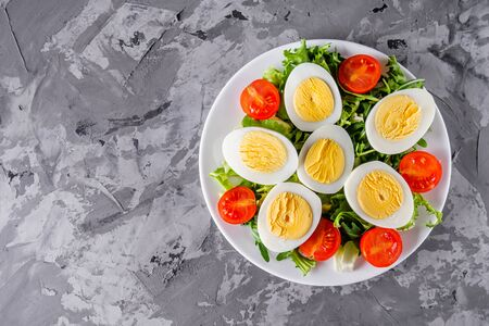 salad with boiled chicken eggs and cherry tomatoes on a stone background. Banque d'images