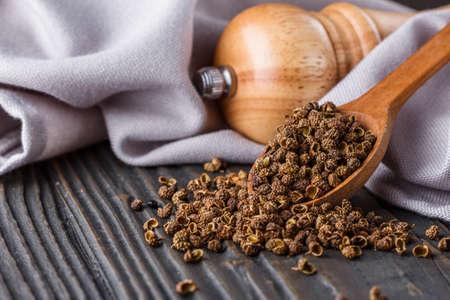 Sichuan pepper on a dark wooden rustic background. Reklamní fotografie