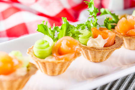 delicious snack tartlets on rustic wooden background.