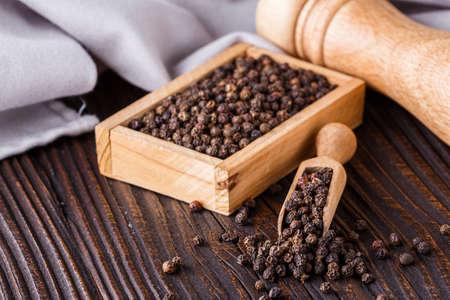 aromatic black pepper on a dark wooden rustic background. Reklamní fotografie - 150873860