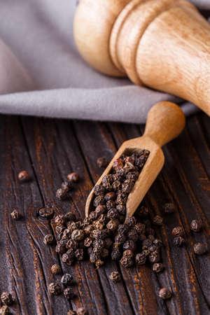 aromatic black pepper on a dark wooden rustic background. Stock fotó
