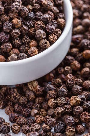 fragrant black pepper on white acrylic background. Stock fotó