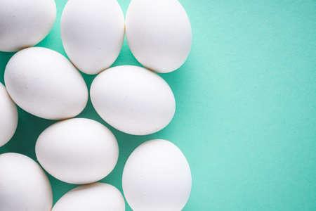 white chicken eggs on green pastel background. Foto de archivo
