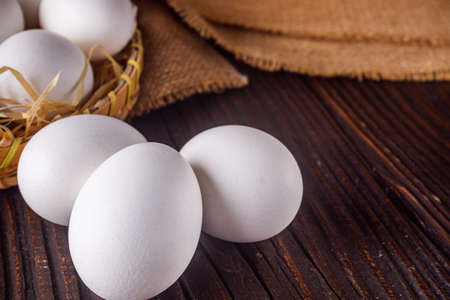white chicken eggs on wooden rustic background.