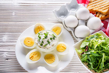 boiled chicken eggs on a white wooden rustic background.