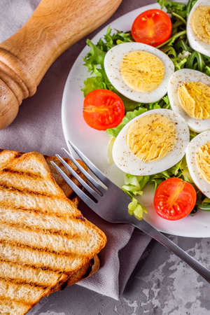 salad with boiled chicken eggs and cherry tomatoes on a stone background. Reklamní fotografie