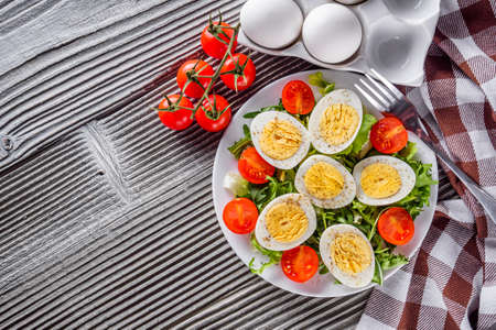 salad with boiled chicken eggs and cherry tomatoes on a wooden rustic background.