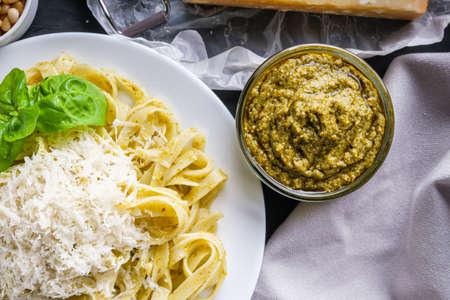 Delicious tagliatelle pasta with pesnto sauce on dark stone background
