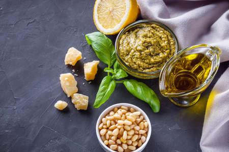 Delicious traditional italian pesto sauce on dark stone background