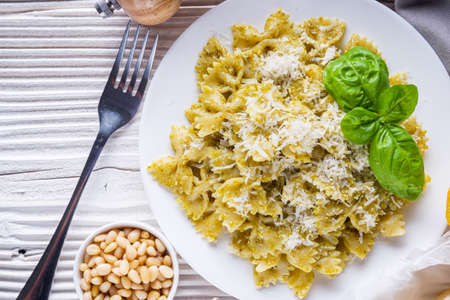 Delicious farfalle pasta with pesto sauce on wooden rustic background Stock fotó