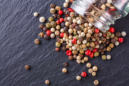 mix of peppercorns on a dark stone background