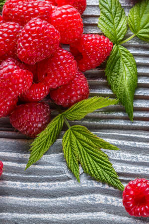 juicy fresh natural raspberries on a gray wooden rustic background
