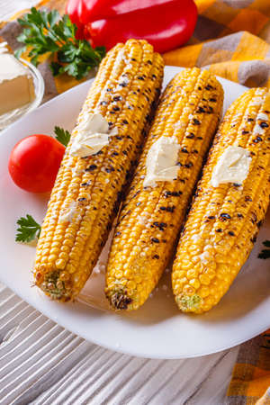 grilled corn cob on white wooden rustic background