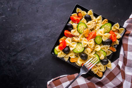 tasty pasta salad with tomato cucumber and olives on a dark stone background Stock fotó