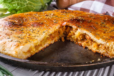 freshly baked cabbage pie on rustic wooden background