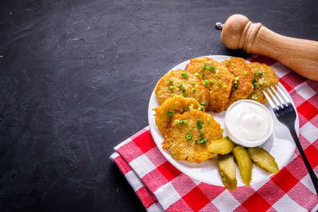Delicious crispy potato pancakes on dark stone background