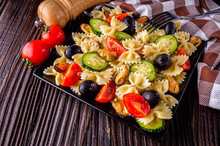 Delicious pasta salad with tomato cucumber and olives on wooden rustic background Stock fotó