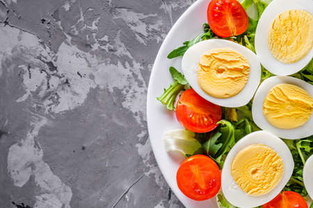 salad with boiled chicken eggs and cherry tomatoes on a stone background