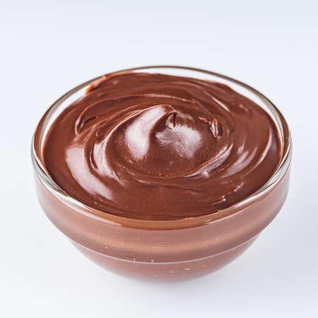 chocolate butter and hazelnuts on a white acrylic background. Reklamní fotografie