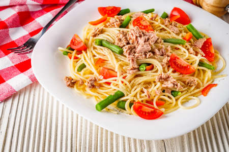delicious traditional Italian pasta with tuna on a white rustic wooden background.