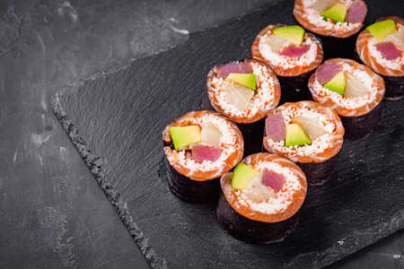 appetizing sushi roll with tuna salmon escolar crab and avocado on a black stone plate.