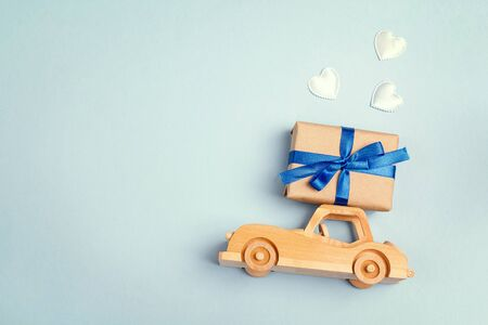 Wooden toy car with a gift box on the roof on blue background. Copy space for text, top view. Fathers day background. Reklamní fotografie