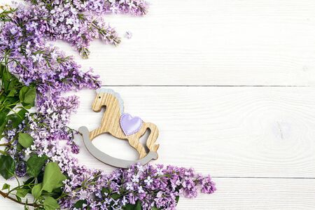 Lilac flowers with toy rocking horse on white wooden background. Top view, flat lay, copy space. Stock Photo
