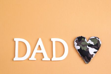 Fathers day background with letters and military heart on yellow. Happy fathers day concept.