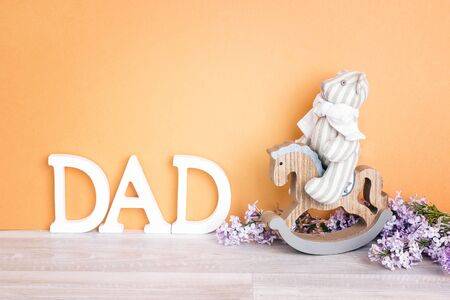 Toy bear on a rocking horse and letters DAD on yellow background. Fathers  Day concept. Copy space.
