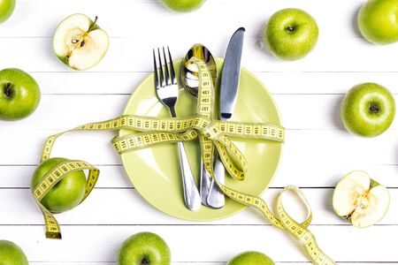 Diet concept table setting with cutlery, yellow measuring tape and green apples on white wooden table.  Weight loss and healthy. 免版税图像