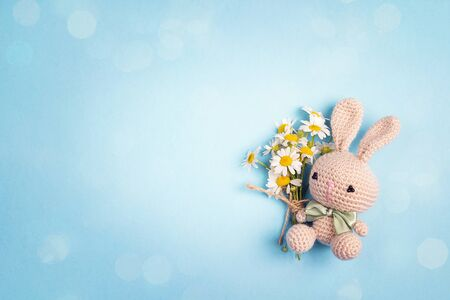 Cute toy bunny with chamomile flowers and copy space on a blue background. Flat lay, top view.