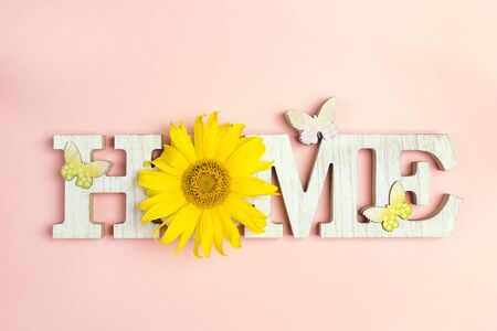 Decorative word Home with butterflies and sunflower on pink background. Copy space. Home sweet home.