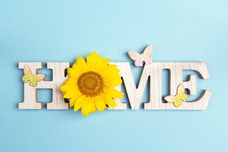 Decorative word Home with butterflies and sunflower on blue background. Copy space. Home sweet home.