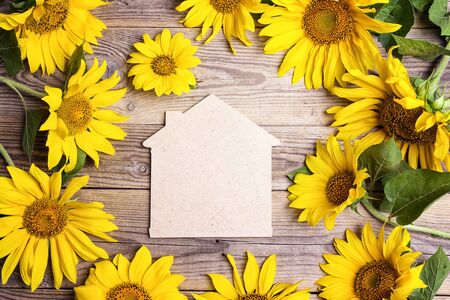 Home symbol with yellow sunflowers on a old wooden backgrounds. Space for text. Top view.