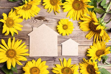 Two home symbols with yellow sunflowers on a old wooden backgrounds. Space for text. Top view. Stock Photo