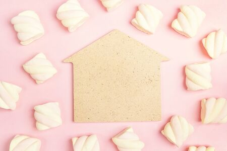 House symbol with spiral marshmallows on pink background. Copy space, flat lay, top view. Home sweet home.