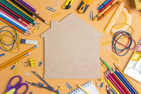 Back to school concept with house symbol and school supplies on yellow background. Copy space, top view.