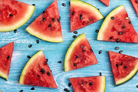 Sliced watermelon on blue wooden background. Flat lay, top view.