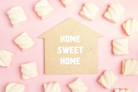 Phrase Home sweet home with spiral marshmallows on pink background. Flat lay, top view. Stockfoto