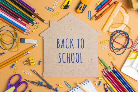 Back to school concept with house symbol and school supplies on yellow background. Top view. Stockfoto
