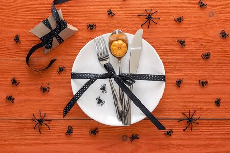Halloween table setting with cutlery, gift box and decorative spiders on orange table. Copy space. Top view.