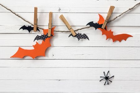 Paper bats hang on clothespins on a white wooden background. Halloween background. Space for text.