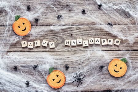 Halloween background with decorative pumpkins, creepy web and spiders on old wooden boards. Festive  concept.
