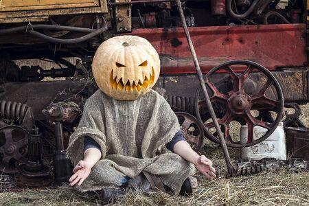 Jack-lantern with a pumpkin on his head meditates near a tractor. Halloween concept. Stock fotó