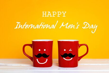 International men's day background with two red coffee mugs with a smiling whiskered faces on a yellow background. Happy coffee men's mugs. Stock Photo