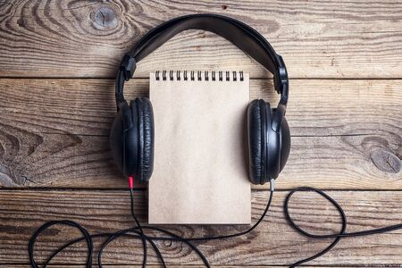 Blank notebook with a headphones on it on wooden background. Top view with space for text. 版權商用圖片